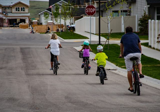 A family riding their bicycles on the street