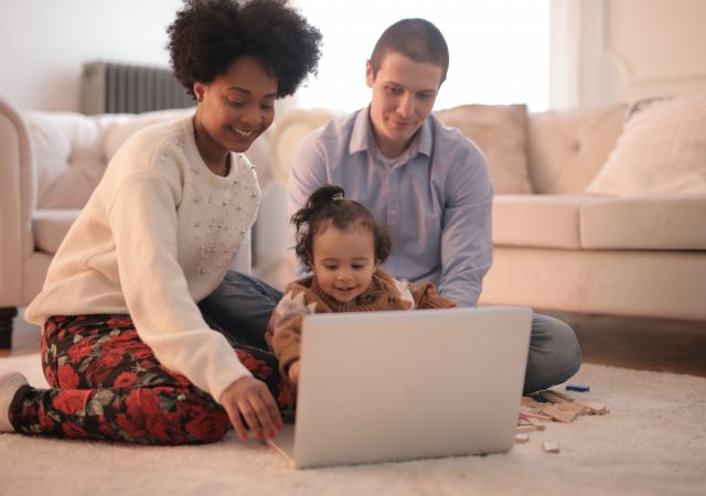 parents and baby looking at laptop